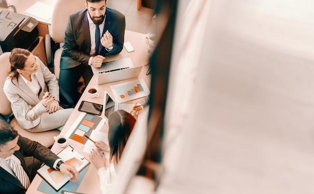 Draufsicht von geschäftsleuten, die besprechung im sitzungssaal haben. unternehmensgeschäftskonzept. teamwork teilt die aufgabe und multipliziert den erfolg.