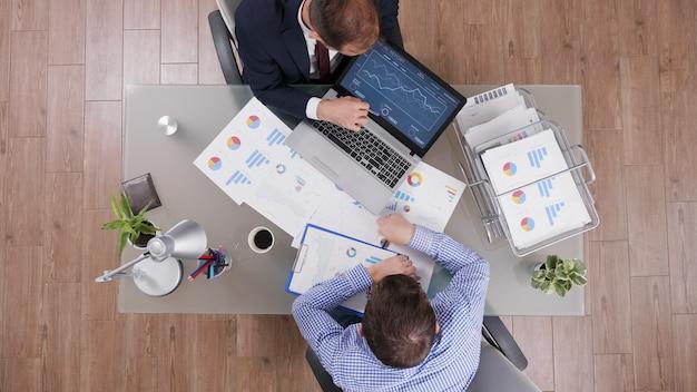 Draufsicht von geschäftsleuten, die managementstatistiken analysieren, während sie an unternehmensinvestitionen arbeiten