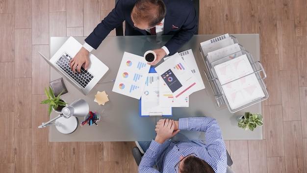 Draufsicht von geschäftsleuten, die über die unternehmensstrategie diskutieren und marketingunterlagen analysieren
