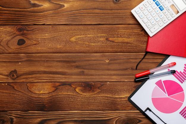 Draufsicht von geschäftspapierdiagrammen auf holztisch mit taschenrechner