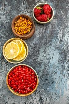 Draufsicht von geschälten granatäpfeln mit anderen früchten auf dunklem hellem hintergrund