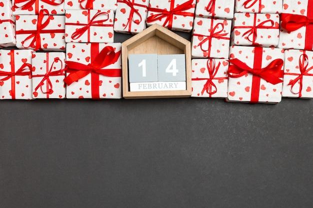 Draufsicht von geschenkboxen mit roten herzen und hölzernem kalender