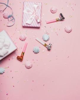 Draufsicht von geschenken; streuen; party horn und süßigkeiten auf rosa hintergrund