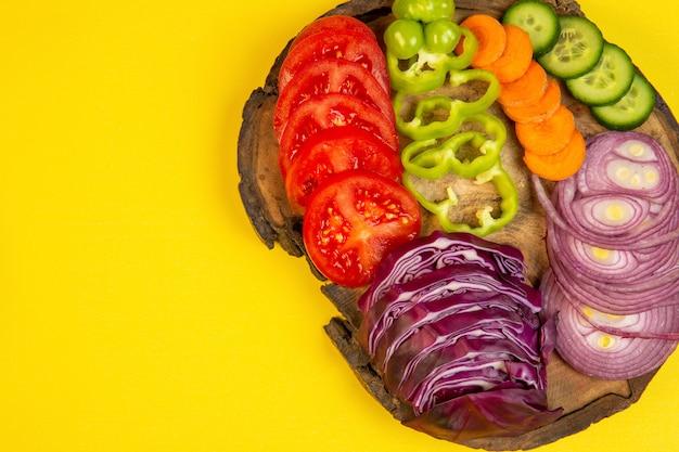 Draufsicht von geschnittenem gemüse rotkohl zwiebeltomaten paprika karotte und gurken auf einem holzbrett auf gelbem j
