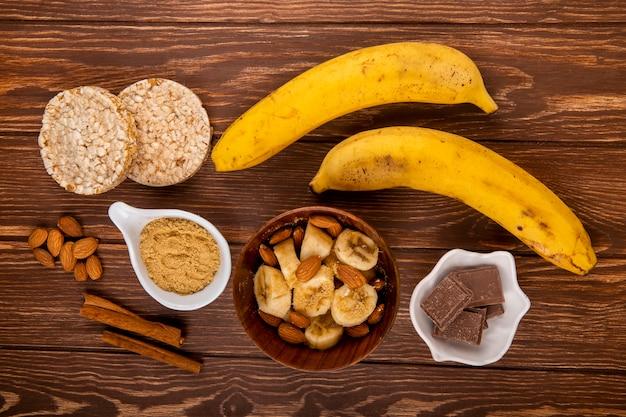 Draufsicht von geschnittenen bananen mit mandel in einer holzschale und frischen reifen bananen mit schokoladen- und reiscrackern auf holz