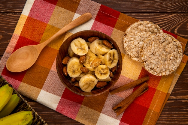 Draufsicht von geschnittenen bananen mit mandel in einer schüssel und holzlöffeln mit reiscrackern und zimtstangen auf rustikalem