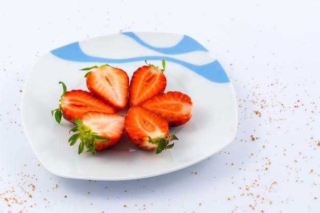 Draufsicht von geschnittenen erdbeeren auf einem weißen teller auf weiß mit braunem zucker