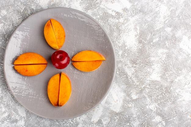 Draufsicht von geschnittenen frischen pfirsichen innerhalb der platte, die auf hellweißer oberfläche ausgekleidet ist