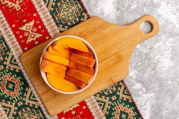 Draufsicht von geschnittenen frischen pfirsichen innerhalb platte auf hellweißer oberfläche