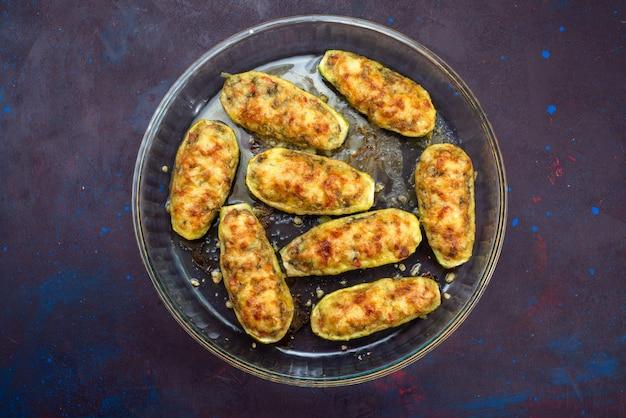 Draufsicht von geschnittenen gekochten kürbissen mit würzigem hackfleisch auf der dunkelblauen oberfläche