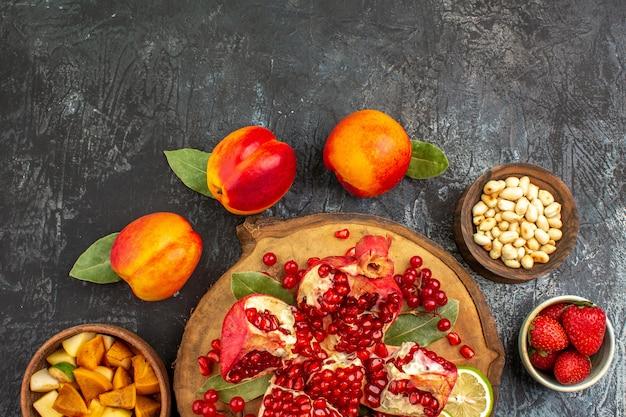 Draufsicht von geschnittenen granatäpfeln mit pfirsichen auf hellem dunklem tisch