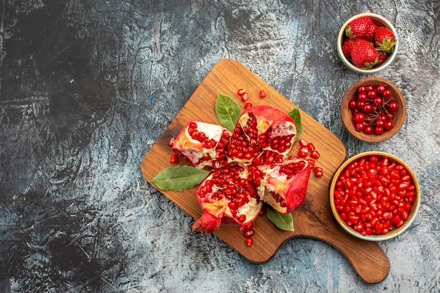 Draufsicht von geschnittenen granatäpfeln mit roten früchten auf einer frischen frucht des dunklen hintergrundbaums