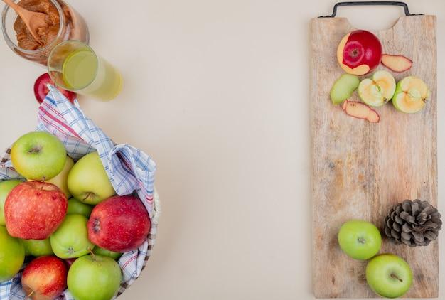 Draufsicht von geschnittenen und ganzen äpfeln mit schale und tannenzapfen auf schneidebrett mit apfelmarmeladenkorb von äpfeln und apfelsaft auf elfenbeinhintergrund mit kopienraum