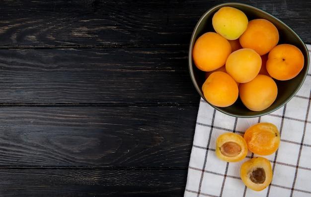 Draufsicht von geschnittenen und ganzen aprikosen auf stoff und hölzernem hintergrund mit kopienraum