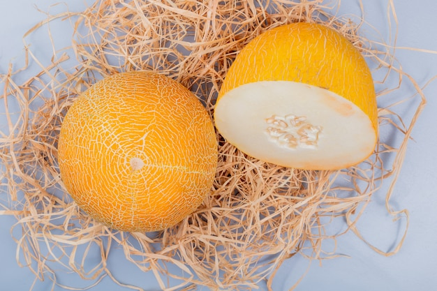 Draufsicht von geschnittenen und ganzen melonen auf stroh und bläulich grauem hintergrund
