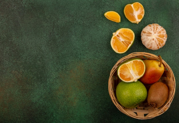 Draufsicht von gesunden und frischen früchten wie apfel-birnen-kiwi auf einem eimer mit mandarinen, die mit kopienraum isoliert werden