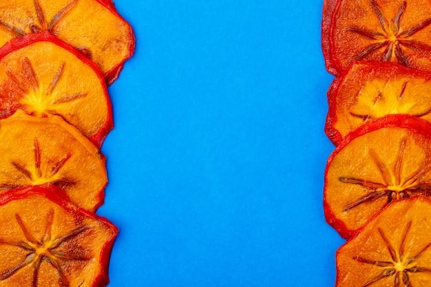 Draufsicht von getrockneten kaki-scheiben, die auf blauem hintergrund mit kopienraum isoliert werden