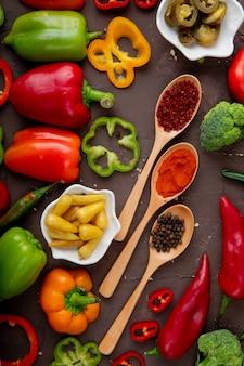 Draufsicht von gewürzen und paprika auf kastanienbraunem hintergrund