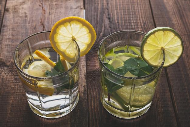Draufsicht von glasgläsern mit sommerlimonade vom wasser, von der zitrone, von der minze und vom eis