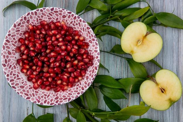 Draufsicht von granatapfelbeeren in schüssel und halbgeschnittenem apfel mit blättern auf holzoberfläche