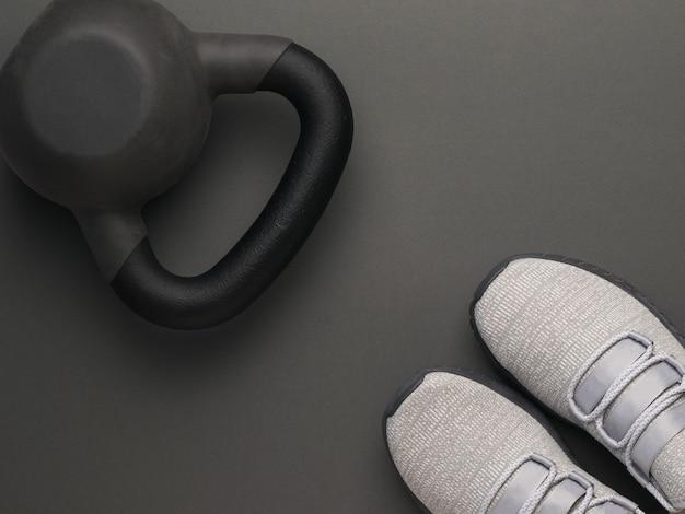 Draufsicht von grauen turnschuhen und einer kettlebell auf einem dunkelgrauen hintergrund. sportlicher lebensstil. flach liegen.