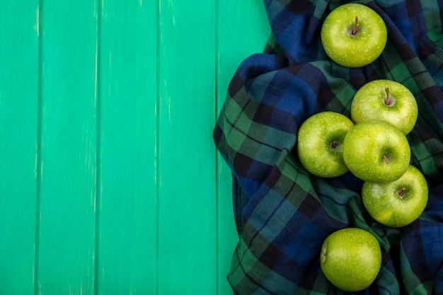 Draufsicht von grünen äpfeln auf kariertem stoff auf grüner oberfläche