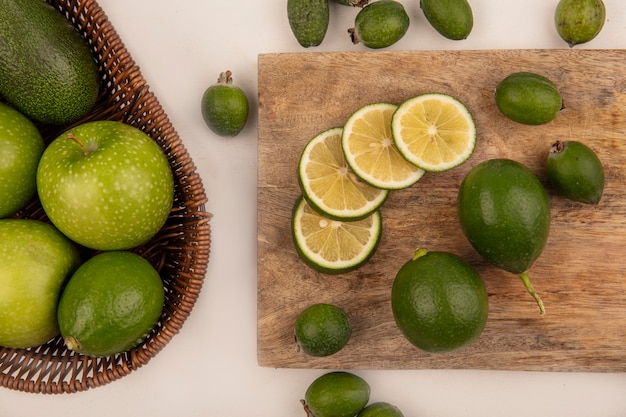 Draufsicht von grünen äpfeln mit avocados auf einem eimer mit limetten und feijoas auf einem hölzernen küchenbrett auf einer weißen wand