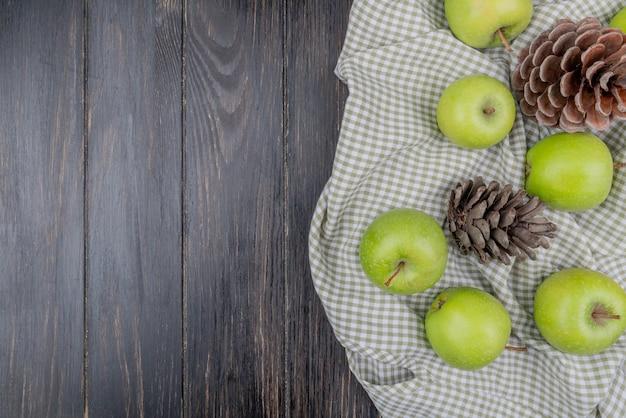 Draufsicht von grünen äpfeln und tannenzapfen auf kariertem stoff und hölzernem hintergrund mit kopienraum
