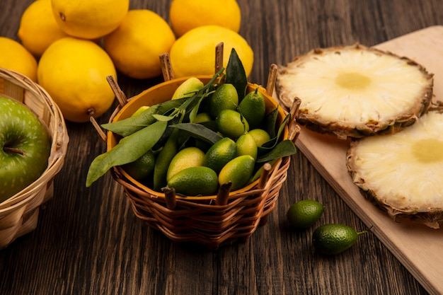 Draufsicht von grünen kinkans mit blättern auf einem eimer mit ananas auf einem hölzernen küchenbrett mit äpfeln auf eimer mit zitronen lokalisiert auf einer holzoberfläche