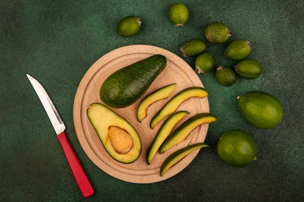 Draufsicht von grünhäutigen avocados mit scheiben auf einem hölzernen küchenbrett mit messer mit limetten und feijoas lokalisiert auf einer grünen wand