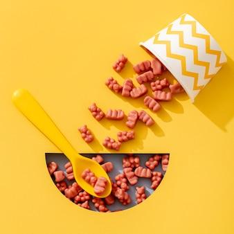 Draufsicht von gummibärchen mit tasse und löffel