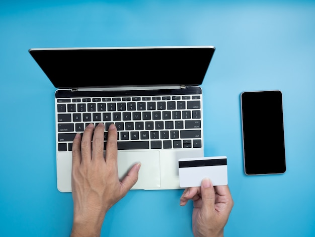 Draufsicht von händen auf laptop und kreditkarte auf blauem hintergrund.
