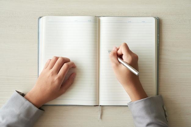 Draufsicht von händen der nicht erkennbaren person bereit, den planer auszufüllen