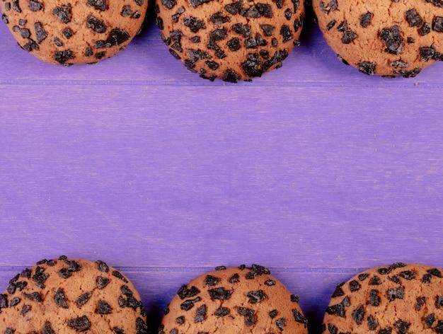Draufsicht von haferkeksen mit schokolade auf lila hölzernem hintergrund mit kopienraum