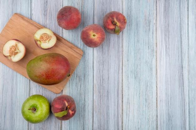 Draufsicht von halben pfirsichen auf einem hölzernen küchenbrett mit mangoapfel auf einer grauen holzoberfläche
