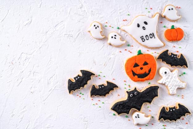 Draufsicht von halloween festlich dekorierten zuckerguss-lebkuchenzuckerplätzchen auf weißem hintergrund mit kopienraum und flachem laylay.