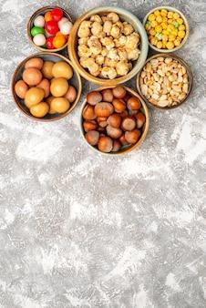 Draufsicht von haselnüssen und erdnüssen mit bonbons auf weißer oberfläche
