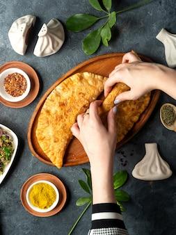 Draufsicht von hausgemachten fleischpasteten belyashi auf einer hölzernen platte auf dunkelheit