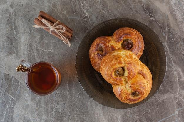 Draufsicht von hausgemachten frischen keksen mit tasse tee auf grau.
