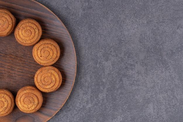 Draufsicht von hausgemachten keksen auf holzteller über graue oberfläche