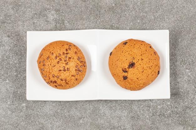 Draufsicht von hausgemachten keksen auf weißem teller.