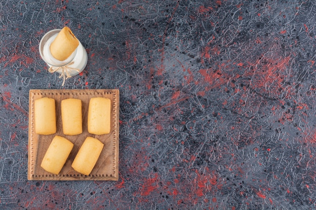 Draufsicht von hausgemachten keksen mit milch auf rustikalem.