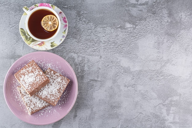 Draufsicht von hausgemachten keksen mit tasse duftendem tee auf grau.
