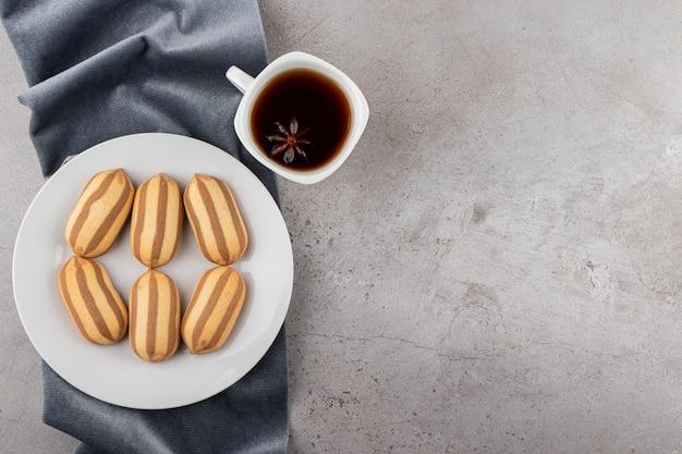 Draufsicht von hausgemachten keksen mit tasse kaffee auf cremefarbenem hintergrund.