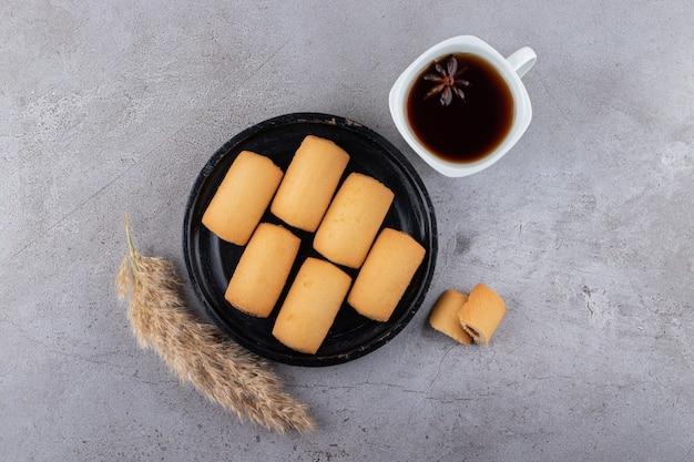 Draufsicht von hausgemachten keksen und duftendem tee auf grauer oberfläche