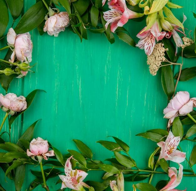 Draufsicht von hellrosa blumen mit blattzweigen auf einer grünen oberfläche