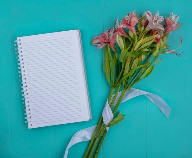 Draufsicht von hellrosa lilien mit einem notizbuch auf einer hellblauen oberfläche
