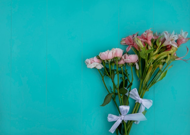 Draufsicht von hellrosa rosen mit lilien auf einer hellblauen oberfläche