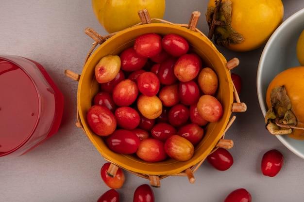 Draufsicht von hellroten und ovalen kornelkirschenfrüchten auf einem eimer mit kakifrüchten auf einer schüssel mit frischem kornelkirschfruchtsaft in einem glas auf einer grauen wand