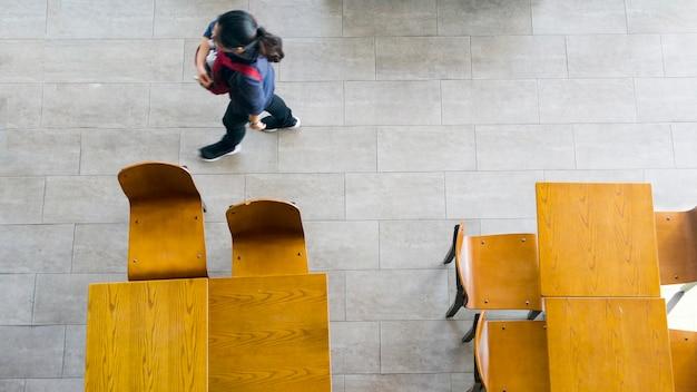 Draufsicht von hölzernen tabellen und von stühlen mit unschärfenleuten gehen